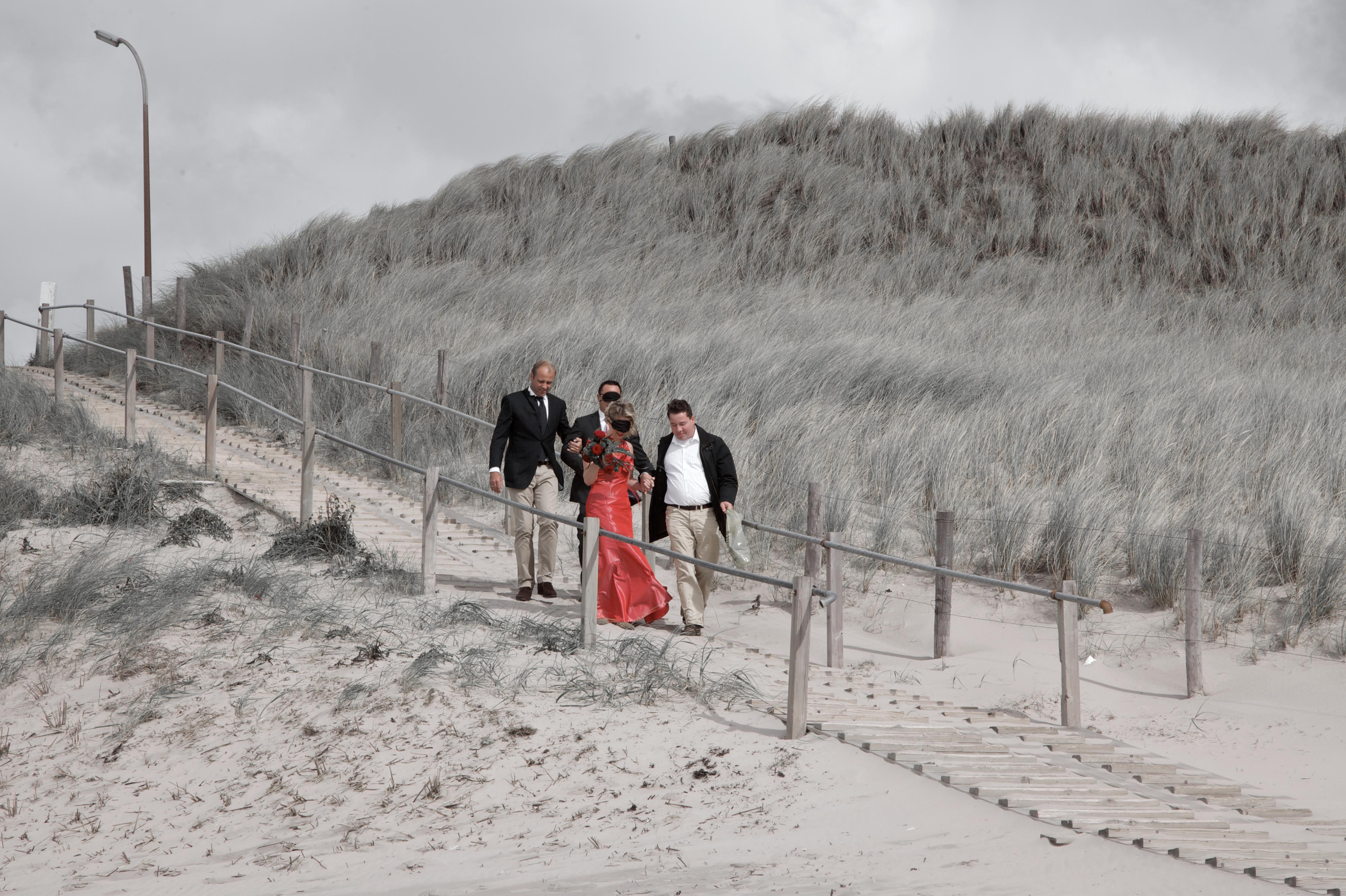 trouwreportage met verrassing op het strand in rode trouwjurk